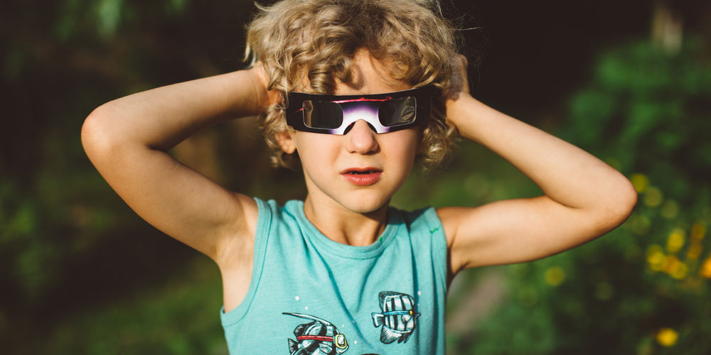 solar eclipse glasses on child